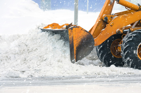 Clearing by the excavator of snow drifts 版權商用圖片
