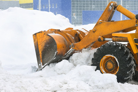 Clearing by the excavator of snow drifts photo