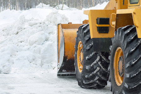 The bulldozer cleans the road after a blizzard photo