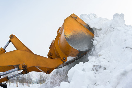 The bulldozer clears away snow drifts photo