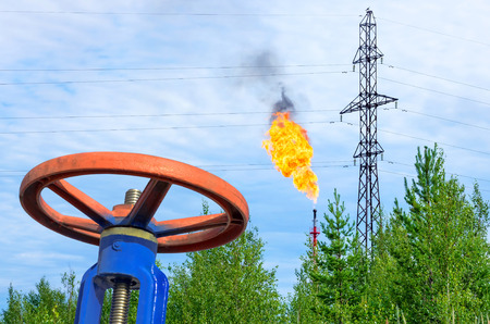 Oil field. The valve with a gas torch on a background. photo