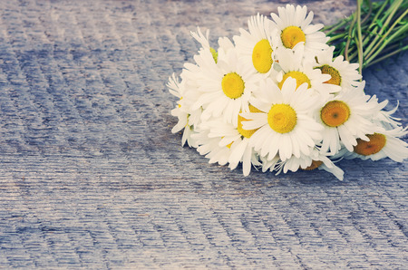 Bouquet of daisies on the board in vintage style photo