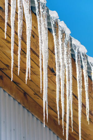 Long icicles hanging from the roof. Spring comes. Stock Photo