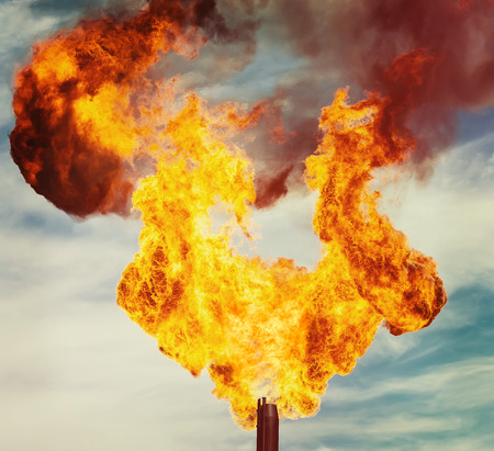 annihilation: Flame of an oil torch in the sky close up Stock Photo