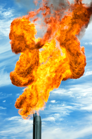 and is favorable: Gas flaring. Torch against the sky. Stock Photo