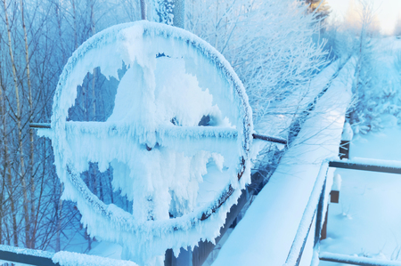 chink: Winter landscape with frosted pipeline and valve Stock Photo