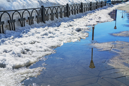 mud and snow: Spring city landscape with thawed snow on the sidewalk Stock Photo