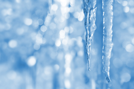 winter thaw: Bright spring background with icicles in the sunlight Stock Photo
