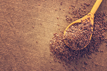 Background of burlap with flax seeds in  wooden spoon