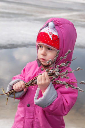 The little girl with  willow bouquet on the river bank photo