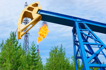 chink: Oil field. Oil rocking a torch gas with the background.