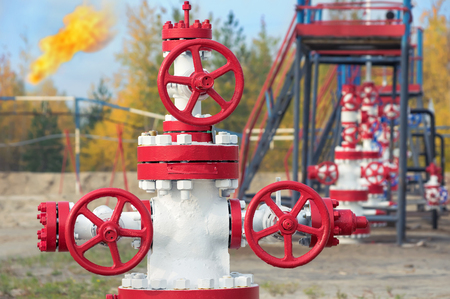 Control valves in the oil field with torch in the background