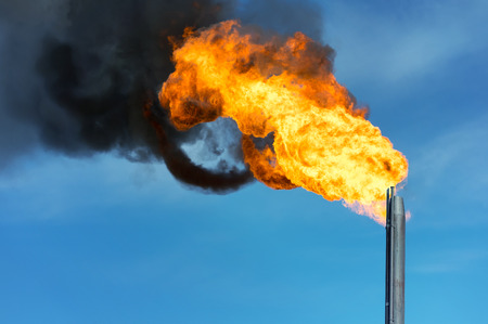annihilation: Torch against the sky. Combustion of associated gas at oil production. Stock Photo