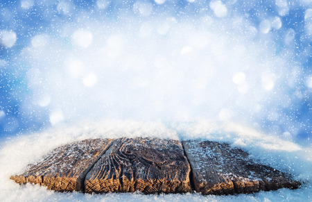 Winter bright background with snow-covered old table