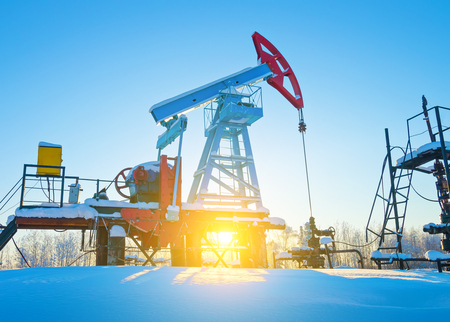 Oil field. Oil pump. The oil pumping unit against the background of morning dawn in the winter. Stock Photo