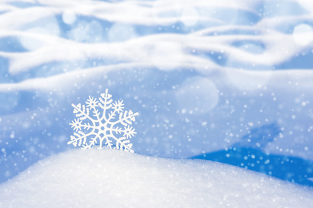 Christmas background with decorative snowflake among snowdrifts