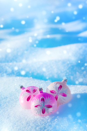 Winter background. Christmas holiday background with balls in snowdrifts.