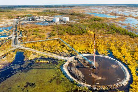 Autumn industrial landscape. Western Siberia. Oil torch. Associated gas burning during oil production. Standard-Bild