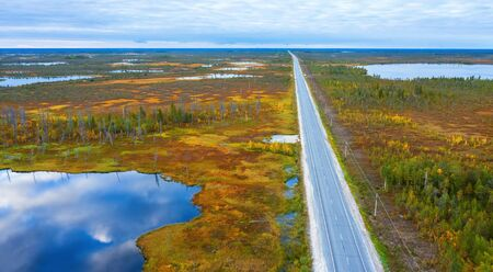 Autumn landscape. West Siberian Plain. Aerial view. Road through endless forests and swamps in Western Siberia.
