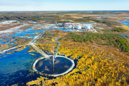 Autumn industrial landscape. Western Siberia. Oil torch. Associated gas burning during oil production. Stock Photo
