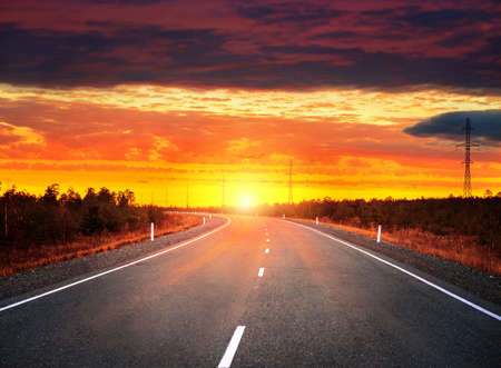 Evening landscape. Car road at sunset with dramatic sky