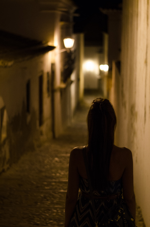 A woman in an old street in Tavira by night, Algarve, Portugal Banque d'images - 119368798