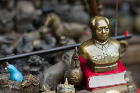 Pingyao, China - 08 13 2016: Vintage and old Chinese Bronze Great Leader Mao Zedong Bust Head small statue on a street market in Pingyao, China