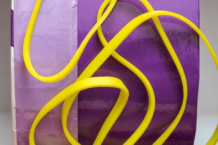 pile of yellow small rubber bands isolated on a purple back ground randomly placed