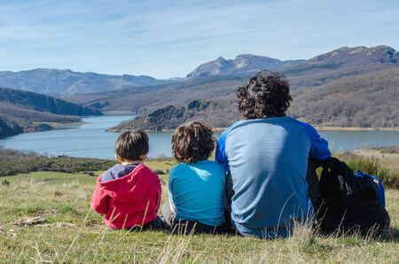 father and his two sons relaxing for a moment and enjoying the views after a hard hiking in the mountains