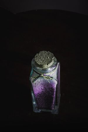 fancy bottle with lavender bath salts for relaxing spa treatments with wooden background 스톡 콘텐츠