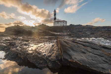 lighthouse with stony foreground during dawn in a winter day with cloudy sky in Menorca, Spain