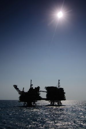 offshore: Offshore oil rig.  Silhouette view in hard sun light and blue sky