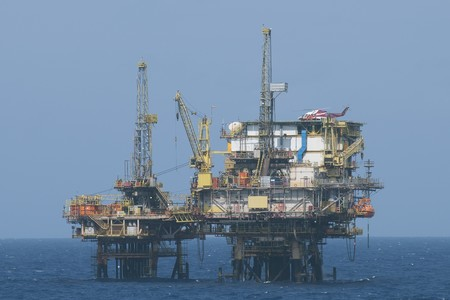 landed: Offshore oil production rig with an helicopter landed on the helideck.