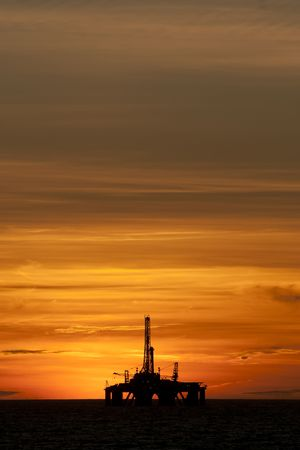Oil rig in offshore area during sunset time. Stock Photo