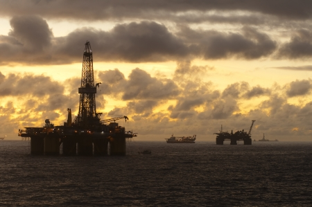 oil rig: Oil rigs and supply vessels in oil rig field in Campos basin, Brazil.  Sunset time