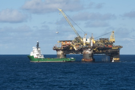 gas supply: offshore oil rig tranfering some container to supply vessel, in Campos Basin, Brazil. Stock Photo
