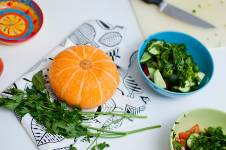 Vegetarian and healthily cooking concept. Fresh ripe vegetables in a kitchen. Pumpkin and parsley