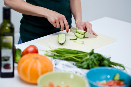 Womans hands cooking in the kitchen, slicing fresh salad. Vegetarian and healthily cooking concept Stock Photo