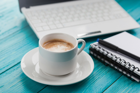 Office items with cup of coffee, notepad, pen and laptop on a blue turquoise table