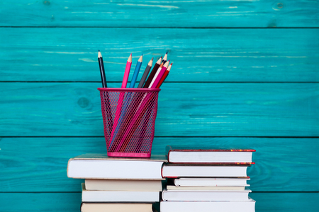 Stack of books and colorful pencils in front of turquoise wooden wall. Back to school idea