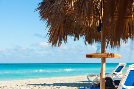 Perfect wild sandy Varadero beach with turquoise sea water and white sand. View through grass palm leaf sun umbrella, nobody