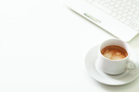 Espacio de trabajo blanco con taza de café y computadora. Concepto de oficina. Luz natural de la mañana. Espacio libre para texto