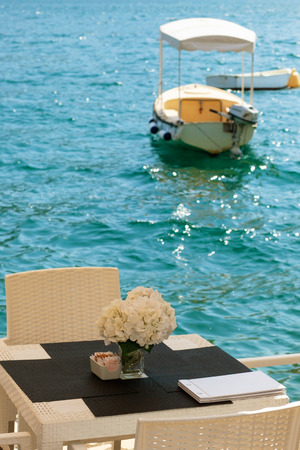 White cafe table on the embankment of Adriatic sea with flowers. View on the boat