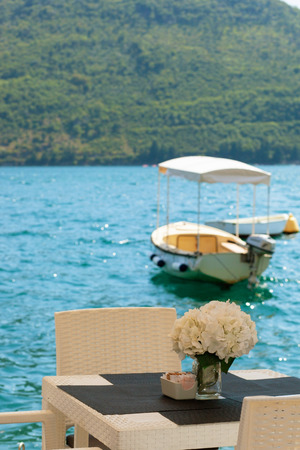 White cafe table on the embankment of Adriatic sea with flowers. View on the boat and montains Banco de Imagens
