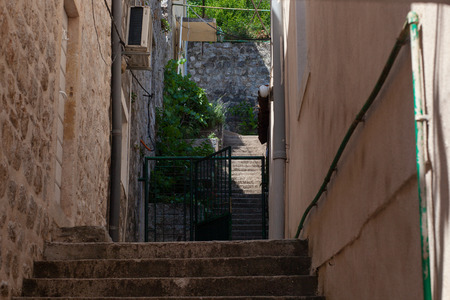 View of an alley with houses of the ancient stone made. Green plants on walls. Narrow street of authentic old town Perast, Montenegro.