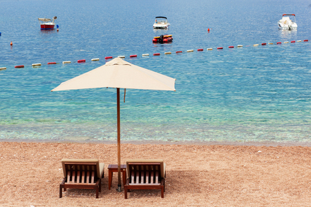 Holiday, travel and vacation concept. The empty beach with two chairs and umbrella. Sea with boats Reklamní fotografie