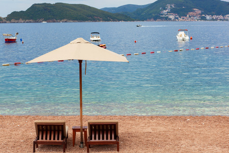 Holiday, travel and vacation concept. The empty beach with two chairs and umbrella. Sea with boats and mountains in a background