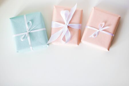 Presents with peach and mint colored craft paper decorated with striped ribbon bows on white background. Holidays concept. Flatlay, Selective focus