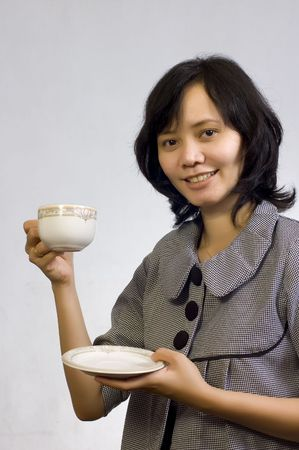 Beautiful Asian Business Woman drink a cup of coffee and sitting at the table photo