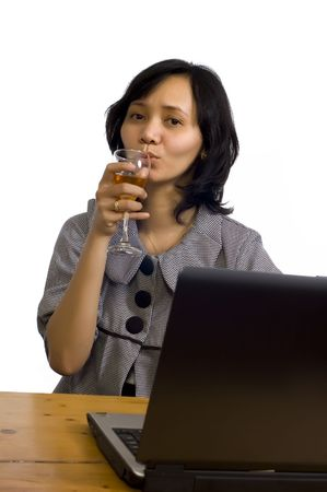 Beautiful asian business woman celebrating her success with wine in front of her computer photo